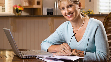 Women smiling at desk with laptop